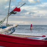 fischerboot an der nordsee im hintergrund zwei windsurfer