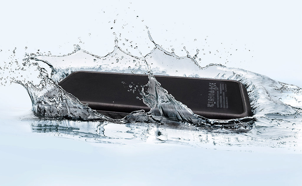 Wasserfeste Powerbank fällt in eine Pfütze klares Wasser